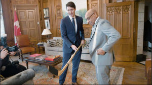 Justin Trudeau och Willy O'Ree beundrar en hockeyklubba.