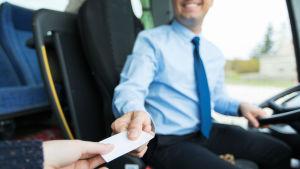 Busschaufför (man ser inte ansiktet) ger en biljett till passagerare (som man ser bara handen på).
