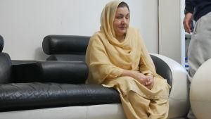 Haseena Ahktar sitter i en soffa och tittar ner i golvet.