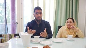 Mamma och sonen sitter vid köksbordet. Mir Omar förklarar någonting och har händerna upplyfta framför sig.
