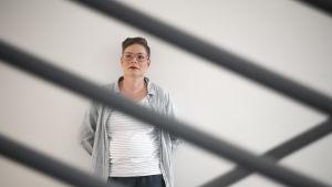 En kvinna står framför en vit vägg. Hon ser åt vänster. Hon ser allvarlig ut. I framgrunden metallstänger.