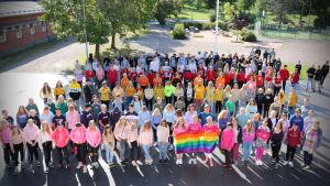 Karis svenska högstadiums elever ute på skolgården med prideflagga.