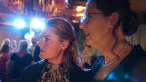 Två kvinnliga kolleger betraktar chockerat något som händer utanför bild.