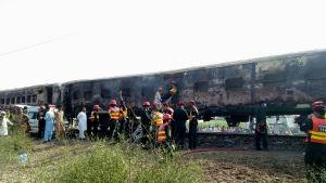 Räddningsarbetare utanför de brandskadade tågvagnarna i Pakistan.