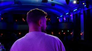 Magnus Betnér tittar ut över en mörk sal från en scen.