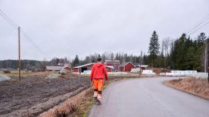 Man går längs väg mot bondgård