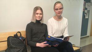 Kaksi opiskelijaa saksan oppikirjan ääressä