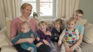 Mamma i soffa med sina fem barn