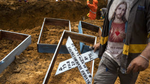 En gravgrävare står framför en massgrav med kors i handen
