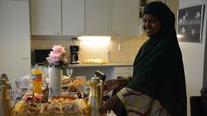 Kvinna dukar fram te och läckerheter.