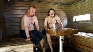 Två män med bar överkropp sitter bredvid varandra på en lave i en träbastu.