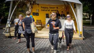 Två personer vandrar bort från en utserveringsdisk med öl i händerna.