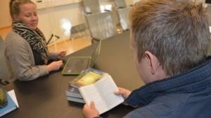 Läsande person vid ett bord.
