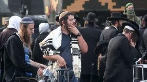 En samling traditionellt klädda judiska pilgrimer knäböjer och ber vid en gränspostering mellan Belarus och Ukraina.