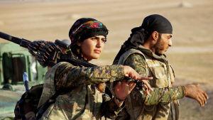 En kvinnlig och en manlig soldat på marsch iklädda kamouflagedräkter. Kvinnan bär ett tungt maskingevär över axeln.