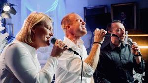 Maria Höglund, Tomas Höglund och Mikael Svarvar sjunger.