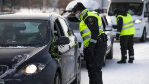 En gränsbevakare i vinterkläder och munskydd talar med en person i en bil,