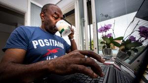 En man distansarbetar och dricker kaffe.