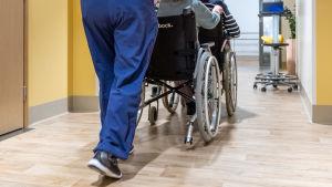 Vårdare skuffar en äldre person i rullstol.