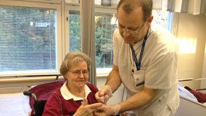 Närvårdare Karl-Erik Dahlin kontrollerar blodsockervärdet på Doris.