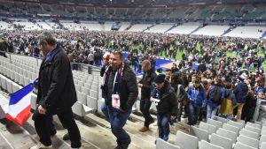 Publiken lämnar fotbollsmatchen Frankrike-Tyskland efter att bomber har exploderat utanför stadion.