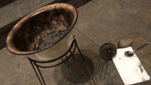Palmkvister bränns i en skål för att bereda askan för askkorset