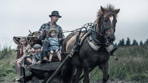 Filmbild av man och barn på hästkärra