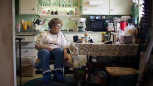 Vanha nainen keittiönpöydän ääressä.