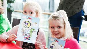 Två barn håller upp kort de pysslat