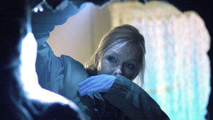 Lena Jaakkola (Anu Sinisalo) raottaa lähikuvassa mustan pussin suuta nenäänsä pidellen. Lenalla on käsissään siniset kumihanskat.