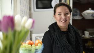 kvinna med frukt och blommor i förgrunden