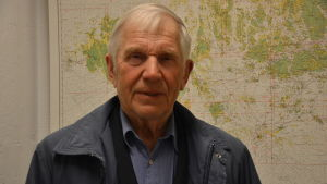 Äldre man med vitt hår och blå jacka står framför ett sjökort över åbolands skärgård.