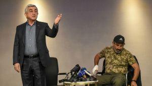 Premiärminister Serzj Sargsian (till vänster) och oppositionsledaren Nikol Pashinian under söndagens tv-sända möte.
