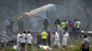 Vrakdelar och räddningspersonal på olycksplatsen