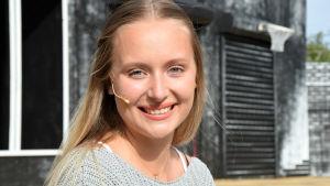 Porträttbild på en leende ung kvinna med långt hår.