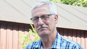 En man med glasögon och blårandig skjorta. Han har mustasch och vitt hår.