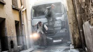 August Walker (Henry Cavill) och Ethan Hunt (Tom Cruise) har kört fast en lastbil mellan två husväggar och hoppar ut genom en krossad vindruta.