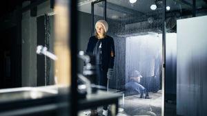 Ella Mettäsen näyttelemä Klara seisoo asunnossaan ja tarkkailee naapureitaan ikkunan läpi.