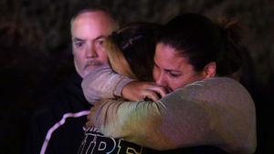 Två personer kramar varandra utanför baren där 13 personer skjutits ihjäl i Thousand Oaks.