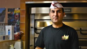 Man iklädd kockhatt står vid en pizzaugn och ser mot kameran.