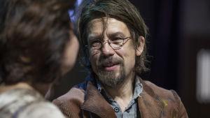 Tommi Erosen näyttelemä Trofimov lähikuvassa. Ikuinen opiskelija tukka pörrössä, silmälasit silmillä.