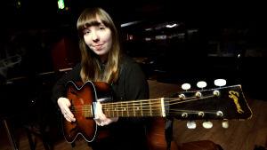 Anna-Stina Jungerstam håller en gammaldags akustisk gitarr.