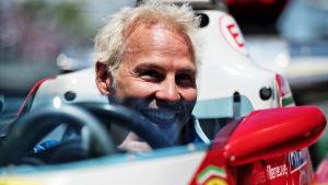 Jacques Villeneuve sitter i en bil och ler