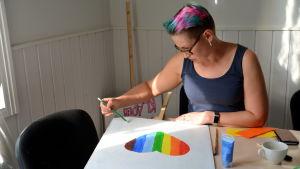 En kvinna målar ett hjärta i regnbågensfärger