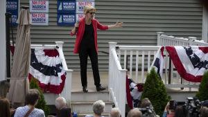 Elisabeth Warren valtalar på en liten flaggprydd terrass i New Hampshire.
