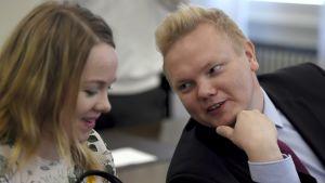 Antti Kurvinen böjer sig fram för att säga någonting åt Katri Kulmuni