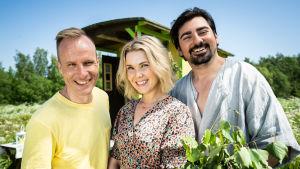 Saunapäivä-ohjelmien kolme juontajaa hymyilevät saunakärryn edessä.