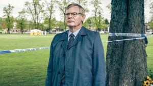Martin Clunesin esittämä poliisihahmo seisoo rikospaikalla nurmikolla.