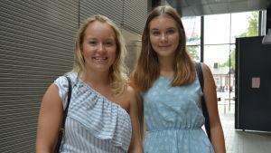 Två unga kvinnor står och ser in i kameran och ler.