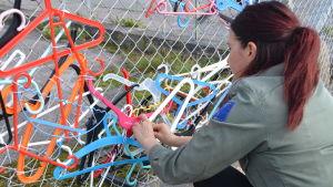Galgar i olika färger har fästs i ett pansarnät. Johanna Kunelius fäster en rosa galg i staketet.